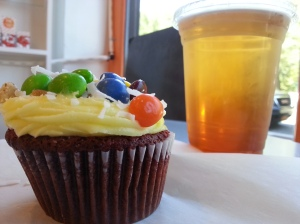 My red velvet cupcake with lemon frosting with Skittles, walnut and coconut flakes with a passion fruit/mango iced tea. (July 24, 2015)
