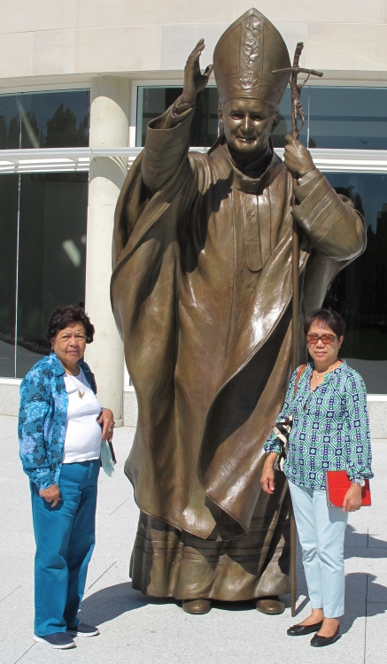 My mother, left, and her friend Thelma stands next to the statue of St. John Paul II.