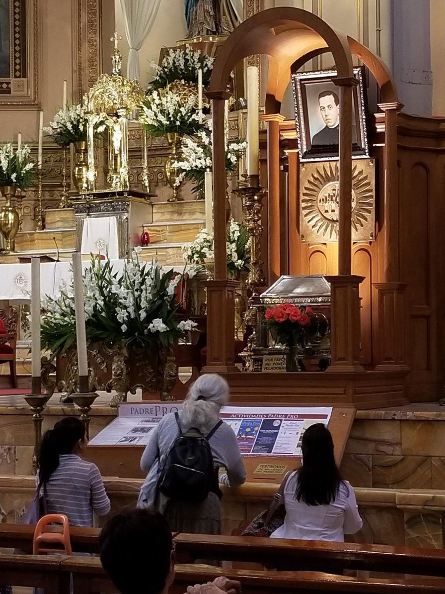 From left, Elaine, Virginia and Alice pray at the relics of Blessed Miguel Pro at Holy Family Church in Mexico City on Monday, July 15, 2019.